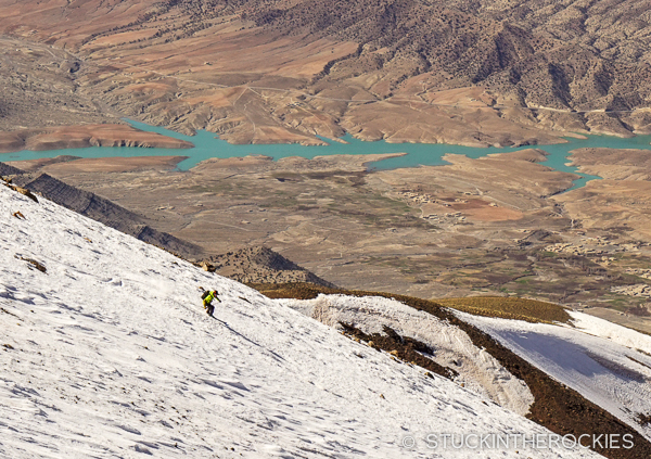 Chris Davenport skis Jbel Ayyachi, with the vast desert background and local reservoir inthe distance.
